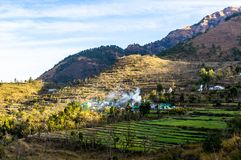 Landscape with village on hillside. Landscape shot of Dehradun with a village on a hillside. The smoke coming from the village, the grassy stepped fields and Stock Image