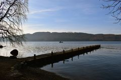 Landscape Shot Lake Windermere - Cumbria. Mid day landscape shot lake windermere in cumbira with small boat in the background on a cold winter day royalty free stock photography