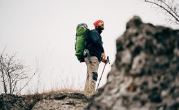 Landscape shot of traveler bearded man trekking and mountaineering during his journey. Tourist young male hiking in mountains. Finished his track. Travel royalty free stock image