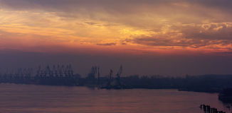 Landscape silhouettes cranes in harbor at sunset in foggy day Royalty Free Stock Photos