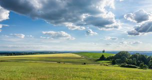 Summer landscape under blue sky with clouds. Romantic view of idyllic countryside with fields, grassland and trees covered by the sun Royalty Free Stock Photography