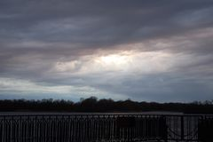 Landscape of the sky covered with dark clouds through which the sun breaks royalty free stock image