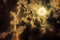 Landscape of sky with dark clouds at nighttime. Beautiful full moon behind partial cloudy with moonlight stock photo