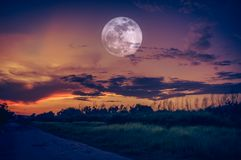 Landscape of sky with full moon at night. Serenity nature backg. Beautiful countryside area at night. Attractive bright full moon on dark sky with cloudy stock photo