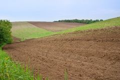 Landscape at slope of cultivated field. Landscape on slope of cultivated field at edge of arable. Agriculture field with plowed soil at hills in spring. Soil Royalty Free Stock Photography