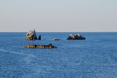 Landscape smooth blue clear water, with rocks Royalty Free Stock Photos
