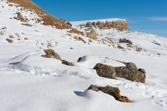 The landscape of snow-covered Caucasian rocks on the Gumbashi Pass. Snow-covered plateau passing into the table mountain with megalithic stones in the Stock Images