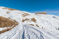 The landscape of snow-covered Caucasian rocks on the Gumbashi Pass. Snow-covered plateau passing into the table mountain with a snow trail in the foreground Stock Image