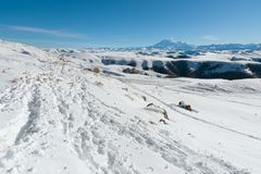The landscape of snow-covered Caucasian rocks on the Gumbashi Pass. Snow covered trail in deep snow with the Caucasian mountain range and the sleeping Elbrus Stock Photo
