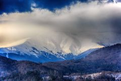 Landscape with snowy mountains under cloudy sky. Romania Royalty Free Stock Images