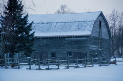Landscape of snowy old grey gambrel barn with icicles. With split cedar rail fence in the foreground and some trees stock photos