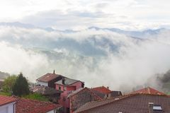 Landscape with some houses and mountains in the fog in Tineo, Asturias, Spain royalty free stock images