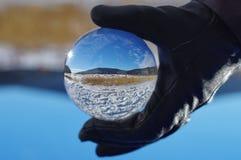 Landscape in sphere glass ball. Beautiful snowy winter landscape in a sphere glass ball Stock Photo