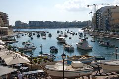 Malta, St. Julian`s: Landscape of the Spinola Bay marine. Landscape of the Spinola Bay marine with colorful traditional Maltese boats and popular coffee bars in Stock Photography