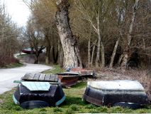 Landscape In the Spring With Rowboats Parked for the Winter. Rowboats along the roadside, parked for the winter with curving road and trees in the spring Stock Photos