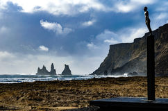 Landscape with statue on the black sand beach of Vik, Iceland. Landscape of bronze seafarer statue on the black sand beach at Vik, Iceland with cliffs in the Stock Photo