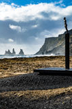 Landscape with statue on the black sand beach of Vik, Iceland. Landscape of bronze seafarer statue on the black sand beach at Vik, Iceland with cliffs in the Royalty Free Stock Photos