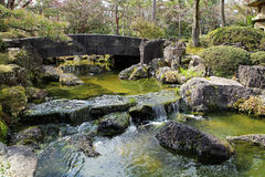 Landscape of stone bridge over garden stream Royalty Free Stock Photo