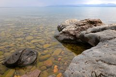 Landscape with a stony shore on the lake. Large stones in clear clear water. stock photo
