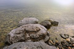 Landscape with a stony shore on the lake. Large stones in clear clear water. stock photography