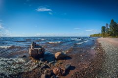 Landscape with stony shore on a lake on sunny day. Big stones in the water. shoreline with trees royalty free stock images