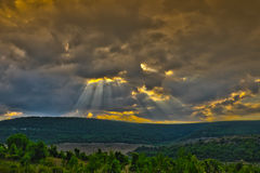 Landscape with storm clouds and the escaping sun beams Stock Images