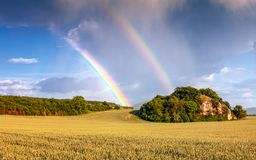 Landscape with dramatic sky and rainbow. Royalty Free Stock Photography