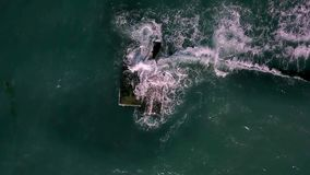 Landscape of stormy sea. Beautiful landscape of the stormy sea. Waves are crashing on the breakwater. Sun is shining on the water surface. Slow motion aerial stock video