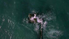 Landscape of stormy sea. Majestic landscape of the stormy sea. Waves are crashing on the breakwater. Sun is shining on the water surface. Slow motion aerial stock footage