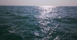 Landscape of stormy sea. Nice landscape of the stormy sea on the clear sky background. Waves are crashing on the breakwater. Sun is shining on the water surface stock video footage