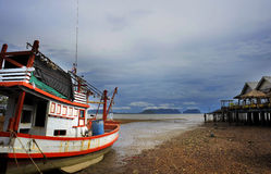 Landscape with stranded boat and vacation resort on low tide beach in Koh Lanta island province of Krabi Stock Photo