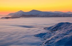 The landscape with a stunning sunset, interesting thick fog and mountains covered with textured snow on a winter day. Royalty Free Stock Image