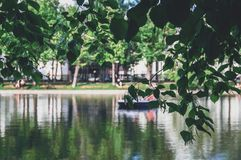 Landscape of the summer city pond surrounded by trees. Reflection of trees in the water. Branches with leaves in the foreground. For different application royalty free stock photos