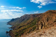 Landscape, summer, day, Crimea, mountains, sea, Cape Megan, view from the top of the coastline and the horizon. Blue sky with white clouds royalty free stock images