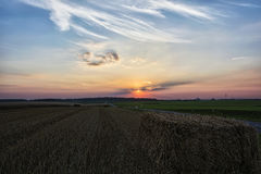 Landscape. The sun sets behind the feathery clouds. Royalty Free Stock Image