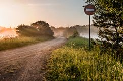 Landscape, sunny dawn with road and road sign Royalty Free Stock Image