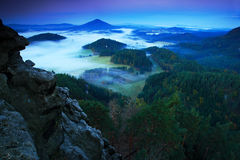 Landscape before sunrise. Cold misty foggy morning in a fall valley of Bohemian Switzerland park. Hills with fog, landscape of Cze Royalty Free Stock Photo