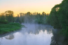 Landscape with sunrise over the river and fog Stock Photo