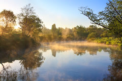 Landscape with sunrise over the river and fog Royalty Free Stock Photos