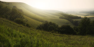 Landscape at sunrise in Summer over rolling hills in countryside Royalty Free Stock Images