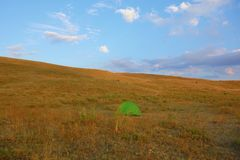 Landscape during sunset in Geghama mountains with a green tent in Armenia stock photography