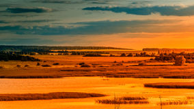 Landscape sunset river meadows field forest hills lit by orange Royalty Free Stock Photos
