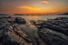 Landscape sunset sea waves line impact rock on the beach, Slow s. Hutter seascape Royalty Free Stock Images