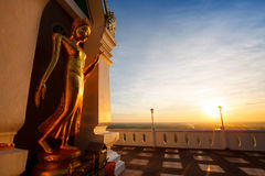 Landscape sunset with standing gold buddha image name is Wat Sra Stock Image