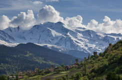 Landscape, with Svan watchtowers and agricultural fields on the background of snow-capped mountain peaks and clouds, Svaneti Royalty Free Stock Images