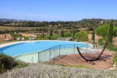 landscape with the swimming pool and hammock at the hills, Tuscany, Italy royalty free stock image
