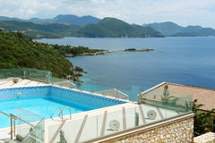 Landscape with swimming pool, the mountains and the blue sea in Royalty Free Stock Photography
