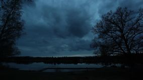 Landscape timelapse at evening by the lake. Landscape and nature timelapse at summer evening in Sweden Europe. Clouds moving slowly in the sky over the lake. A stock footage