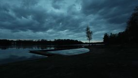 Landscape timelapse at evening by the lake. Landscape and nature timelapse at summer evening in Sweden Europe. Clouds moving slowly in the sky over the lake. A stock video