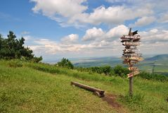 Landscape on top of the mountain on a clear summer day. Post with pointers cities and wooden bench on the top of Mashuk mountain, Caucasus, Russia Royalty Free Stock Images